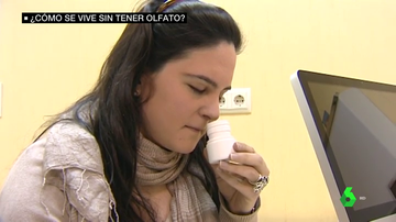 Imagen de una joven oliendo un frasco
