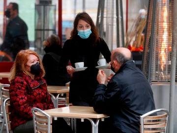 Una camarera sirve a dos clientes en una terraza de Valencia.