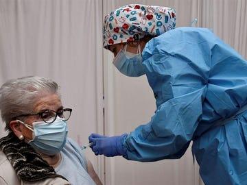 Una sanitaria vacuna a una mujer contra el coronavirus