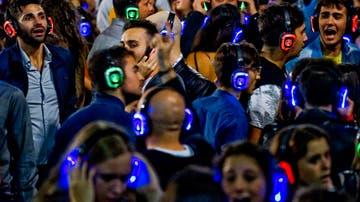 """Centenares de jóvenes bailan al ritmo de la música, a través de auriculares, en la plaza Municipio de Nápoles, Italia, durante la celebración de una """"Fiesta Silenciosa"""""""