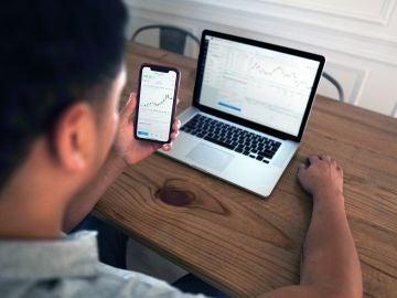 Un hombre realiza unas gestiones con su ordenador y su teléfono móvil