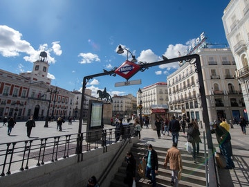 Ciudadanos caminan por la Puerta del Sol, en Madrid