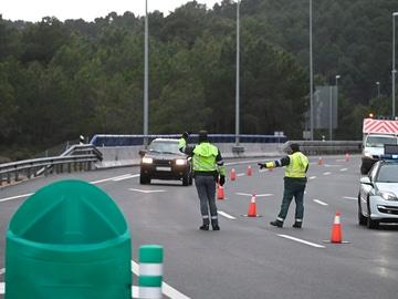 Varios guardias civiles de tráfico dan el alto a un vehículo en un control de carretera