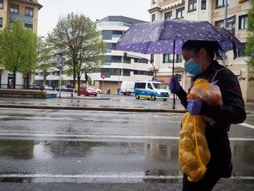 Una mujer se protege de la lluvia con un paraguas mientras camina con una bolsa de patatas durante el Martes Santo
