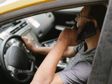 Un hombre habla por teléfono mientras conduce