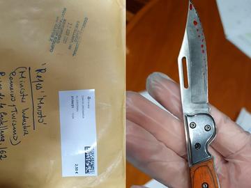 Imagen del sobre y la navaja en la mano enguantada de la policía científica