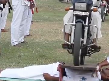 Motocicleta pasando por encima del profesor karateca indio