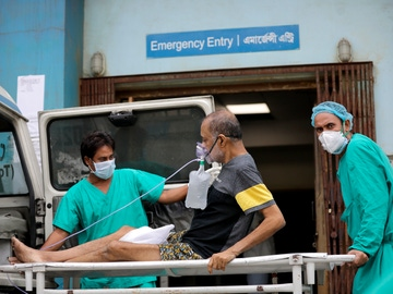 Dos sanitarios atienden a un paciente con COVID-19 en el hospital de Kolkata, en La India