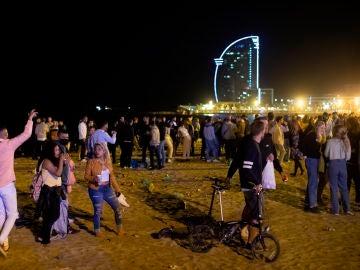 Varios jóvenes recogen sus pertenencias en la playa de la Barceloneta mientras la policía los desaloja