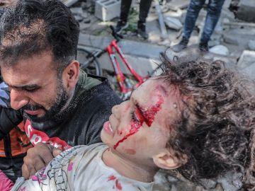 Un padre palestino saca a su hija herida de los escombros de una casa destruida tras un ataque aéreo israelí