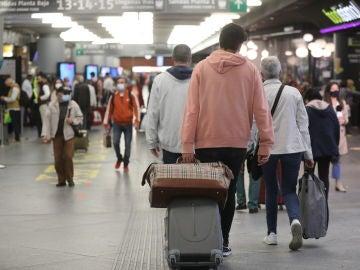 Varias personas caminan con su equipaje por la estación de Madrid - Puerta de Atocha, a 14 de mayo de 2021, en Madrid