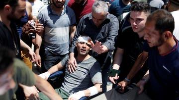 Los equipos de rescate ayudan a un hombre después de sacarlo de los escombros de un edificio en el lugar de los ataques aéreos israelíes en Gaza