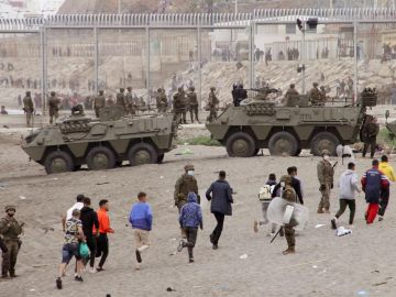 Miembros del Ejército de Tierra dirigen a un grupo de inmigrantes que han logrado cruzar