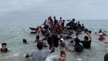 Un grupo de personas se hacen con una embarcación de las autoridades marroquíes en la playa de la localidad de Fnideq