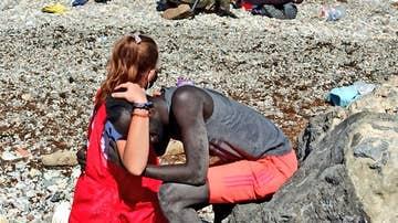 Una mujer de Cruz Roja abraza a un migrante que acaba de llegar a suelo Español