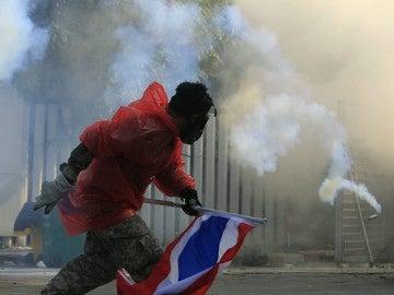 Un manifestante lanza gas lacrimógeno contra una barricada de la policía