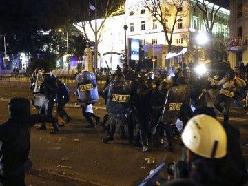 Un joven lanza un objeto a diversos agentes de la policía antidisturbio al término del 22M