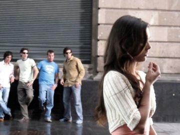 Un grupo de hombres observa a una mujer en la vía pública.