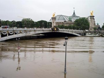 Vista general de lámparas parcialmente sumergidas junto al puente Alexandre III en el río Sena en París