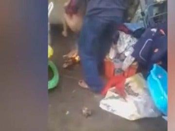 Momento del vídeo en el que se aprecia cómo el padre quema los genitales a su hijastro