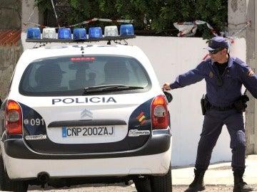 Un agente de Policía junto a un vehículo del cuerpo
