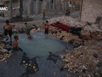 Un grupo de niños sirios juega en torno al cráter de una bomba convertido en piscina en Alepo