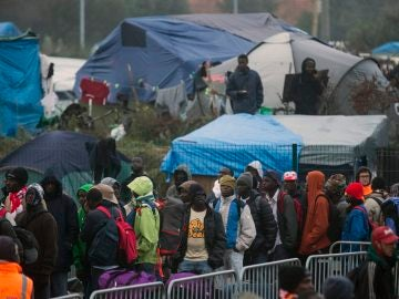 """Varios migrantes esperan para su evacuación en el centro de recepción de corta estancia en el campamento conocido como """"La Jungla"""" durante su desmantelamiento en Calais"""
