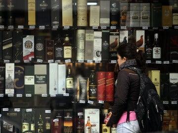 Imagen de archivo de una mujer que observa unas botellas de alcohol expuestas en una vitrina de una tienda