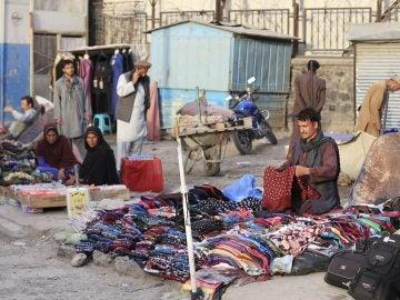 Varias personas venden ropa de segunda mano en una calle de Kabul, Afganistán
