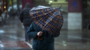 Una persona intenta taparse con un paraguas