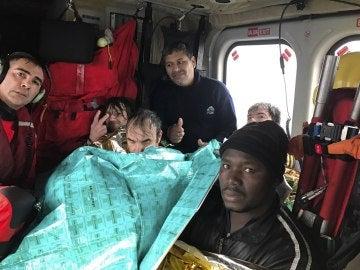 Fotografía facilitada por Salvamento Marítimo de los tripulantes, a bordo del helicóptero Helimer 211 de Salvamento, tras ser rescatados