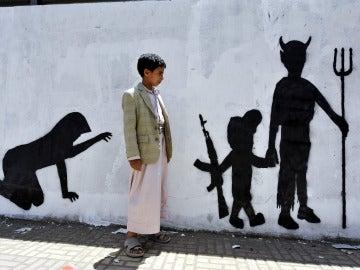 Un niño yemení observa el grafiti de la pared en la que se muestra a un niño soldado caminando de la mano de un demonio