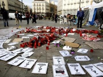 Detalle de flores,zapatos y carteles en una acampada contra la violencia machista en la Puerta del Sol de Madrid.