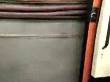 Frame 17.697221 de: Viajan en el Metro de Madrid en un tren con las puertas abiertas durante varias estaciones