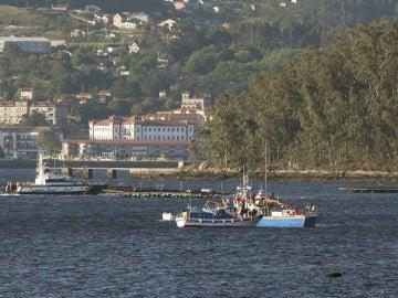 Imagen de una embarcación de la Guardia Civil junto a varias bateas