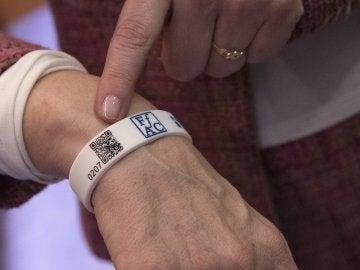 La presidenta de la Federació d'Associacions de familiars d'Alzheimer de Catalunya (FAFAC), Immaculada Fernández, posa con la pulsera de silicona con un código QR