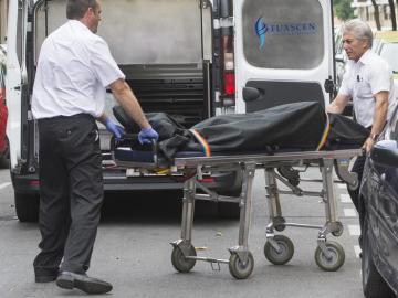 Operarios de la funeraria retirando el cadáver