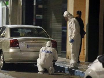 Agentes de la Policía Científica inspeccionan las inmediaciones de la vivienda en Elda