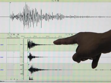 Un sismólogo señala un sismógrafo