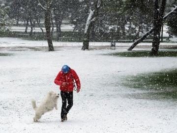 Un hombre pasea con su perro por el parque Emperatriz María de Austria, en Carabanchel,