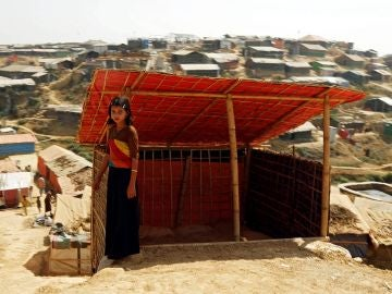 Una niña rohinyá posa delante de su tienda en un campamento en Bangladesh