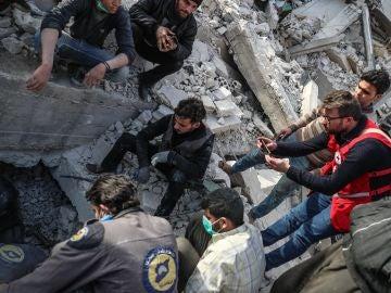 Miembros de Defensa Civil Siria mientras buscan el cuerpo de una víctima