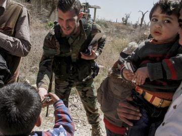 Varios soldados sirios ayudan en la evacuación de un nuevo grupo de civiles de Guta Oriental