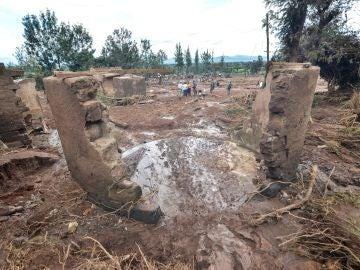 Varias personas pasan entre las casas destruidas por las aguas tras destruirse la presa
