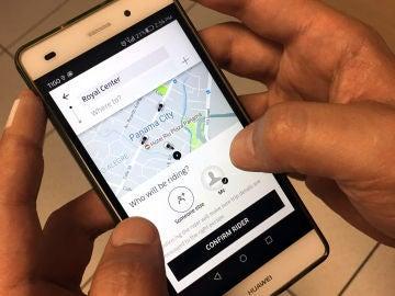 Un usuario de Uber utiliza un teléfono móvil.