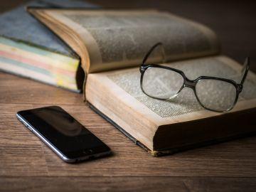 Imagen de un libro, unas gafas y un teléfono móvil