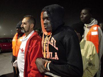 Imagen de archivo de migrantes acompañados de miembros de Cruz Roja