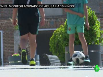 Dos niños juegan a la pelota en la calle