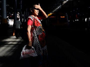 Mujer india esperando al transporte público