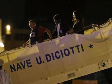 Guardias costeros escoltan a dos migrantes que desembarcan del Diciotti en el puerto de Trapani